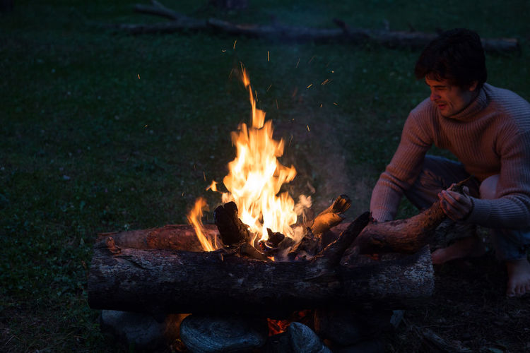 Man by campfire on field