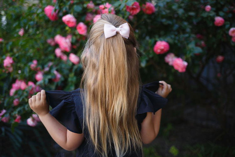 Rear view of girl looking at flowers outdoors
