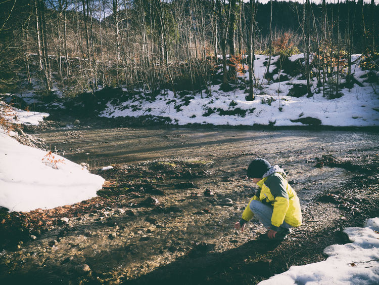 kid at the shore of a winterly river Bavaria Icy Water Nature Sunny Winter Winter Scene At The Shore Cold River Kid Kid Playing Kid Playing In Nature Mountains River Snow Thoughtful Thoughtful Kid Water Woods