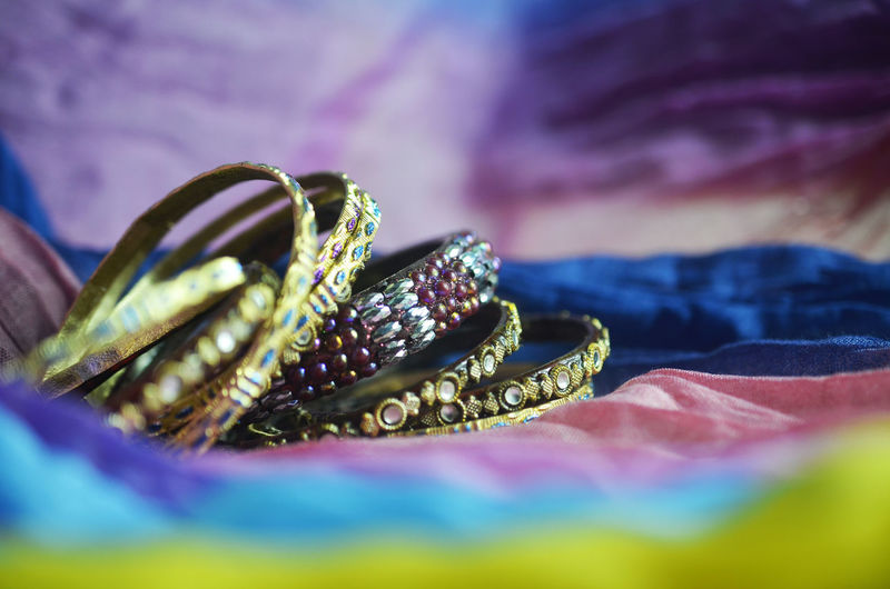 Close up indian bangle jewelry on colourful textiles