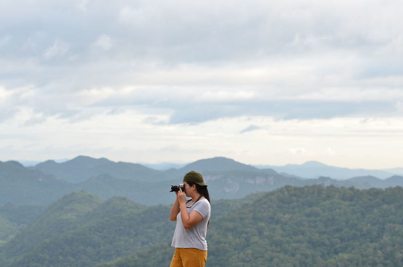 Man photographing with camera standing on mountain