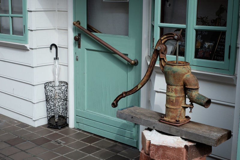 Rusty water pump outside house