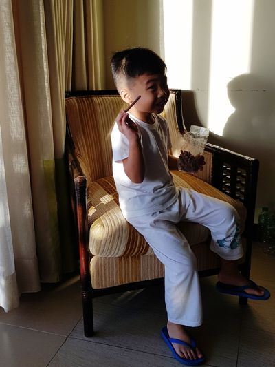 Boy Holding Sticks While Sitting On Chair At Home