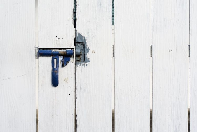 Full Frame Shot Of White Wooden Gate Fence With Blue Metallic Latch