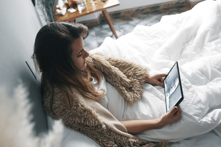 High angle view of woman using digital tablet while sitting on bed