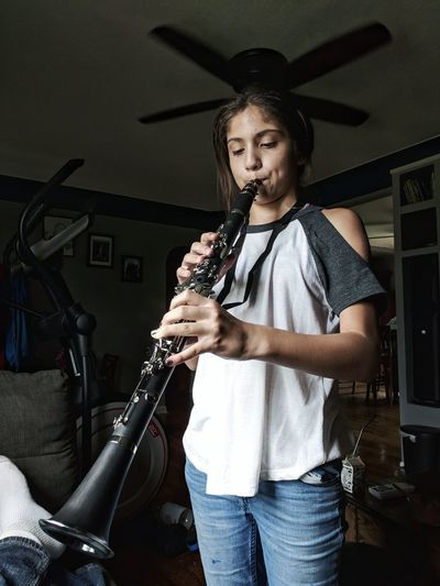 Girl Playing Musical Instrument While Standing At Home