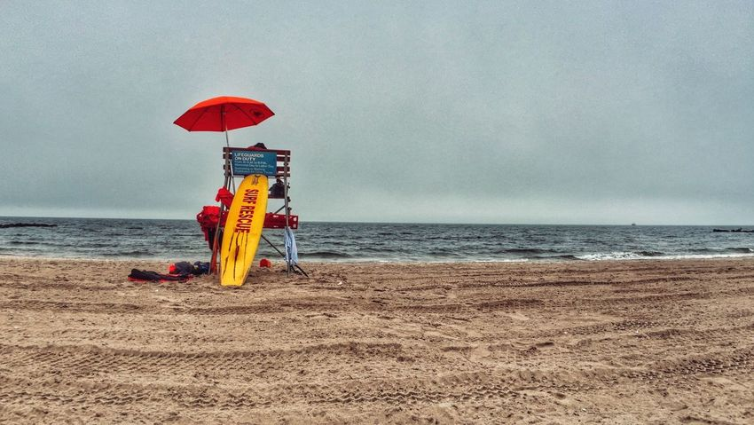 Paint The Town Yellow Beach Sea Horizon Over Water Sand Water Nature Day Protection Real People Beauty In Nature Coney Island New York City Lifesaver Lifeguard  Surfboard oOutdoorstTranquilitysSkymMenpPeople