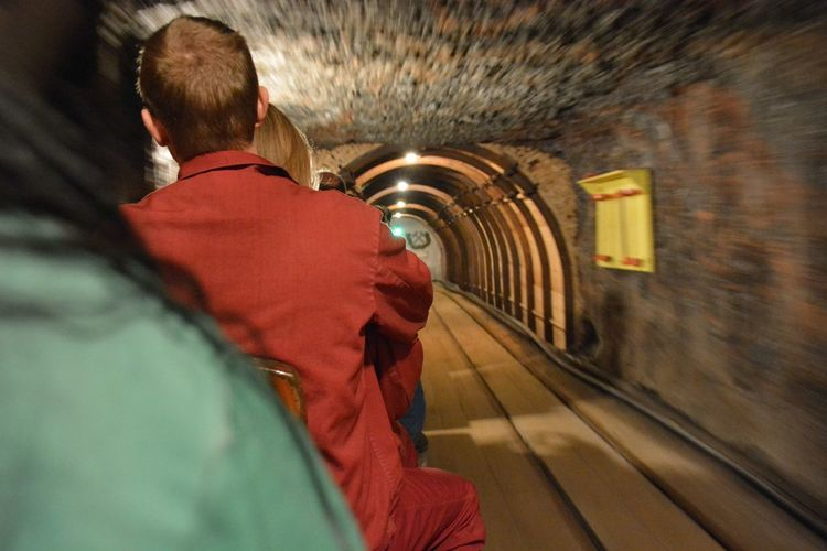 Rear view of people in tunnel