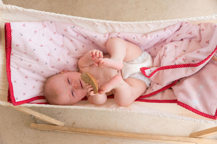 european baby with blue eyes and a piece of bread in hammock Caucasian European  Hammock Day Bread Pink Color View From Above Baby Young Babyhood Child Childhood Real People Innocence Cute One Person Blanket Lying Down Lying On Back Lying Toddler  Relaxation High Angle View Beginnings Having Fun Comfortable