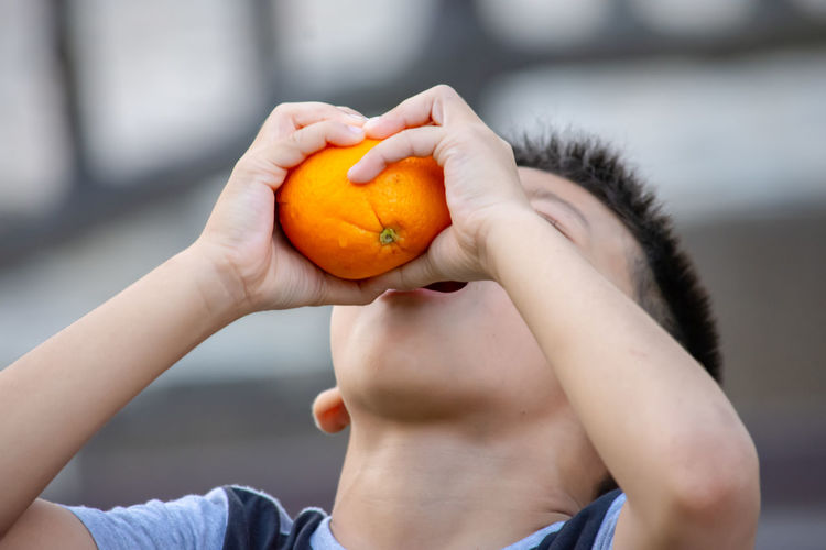 Hand holding orange and squeeze the juice into the mouth of a boy. Focus On Foreground Holding One Person Healthy Eating Food And Drink Close-up Wellbeing Child Orange Color Fruit Childhood Food Human Hand Headshot Boys Day Freshness Males  Hand Orange Outdoors Innocence