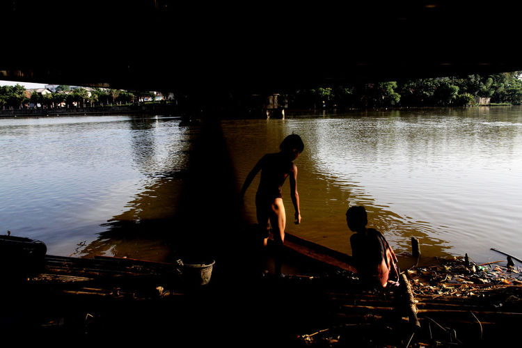 Homeless Kids under the Bridge Bad Condition Boys Dirty Homeless Lifestyles Poverty River River Bank  Shower Silhouette Slum Swimming Togetherness Unhygienic Water Waterday