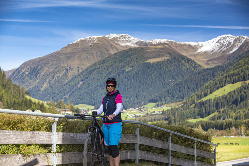 Portrait of woman standing with bicycle by railing against mountains
