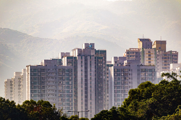 Buildings in city against mountains