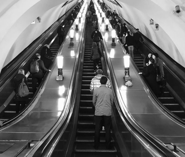 People Standing On Escalator At Subway Station