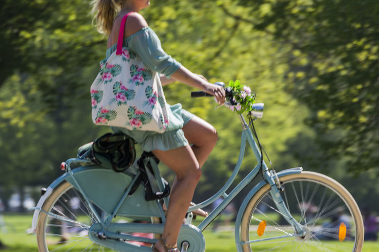 Low Section Of Young Woman Riding Bicycle In Park