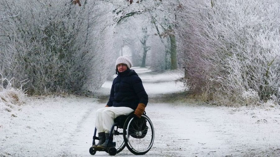 Woman on wheelchair over snow covered road amidst bare trees