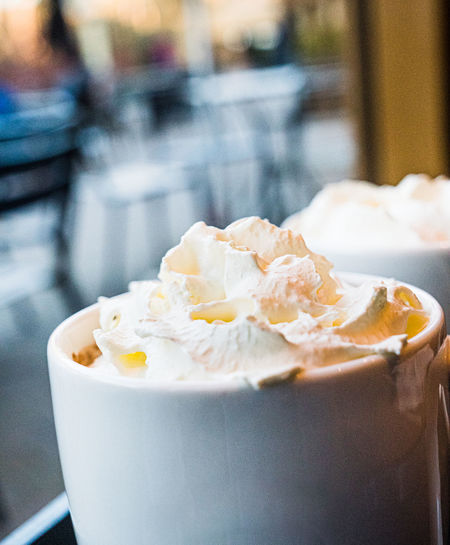 Close-up of a mug of hot chocolate with cream on a table
