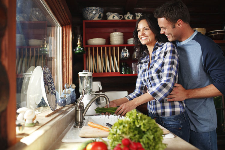 Man and woman standing by food in kitchen