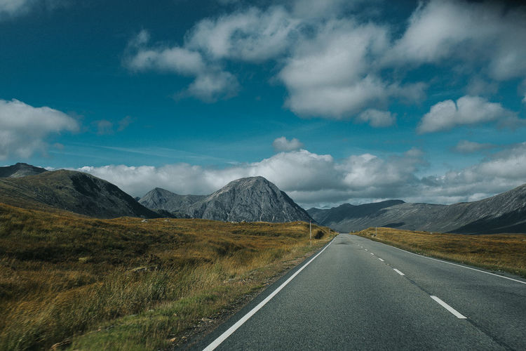 Empty Road Leading Towards Mountains Against Cloudy Sky