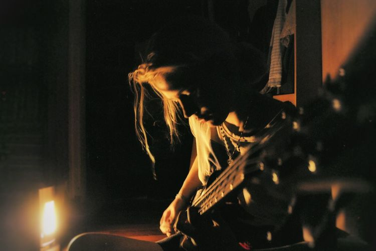 Woman playing guitar while sitting in darkroom