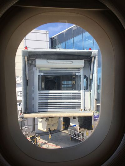 Passenger boarding bridge seen through airplane window