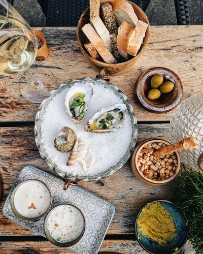 Delicious spread of seafood and white wine Dinner Lunch Meal Menu Tapas Appetizer Fish Food Food And Drink Freshness High Angle View Oyster  Seafood Table Wine Wood - Material