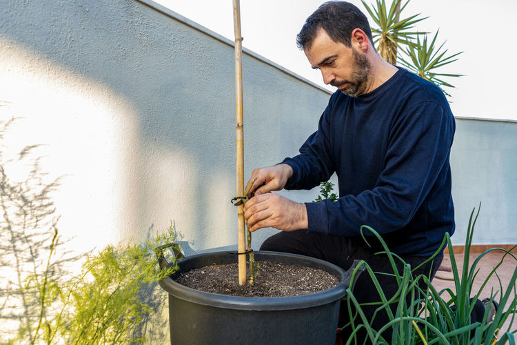 Man working in potted plant at yard