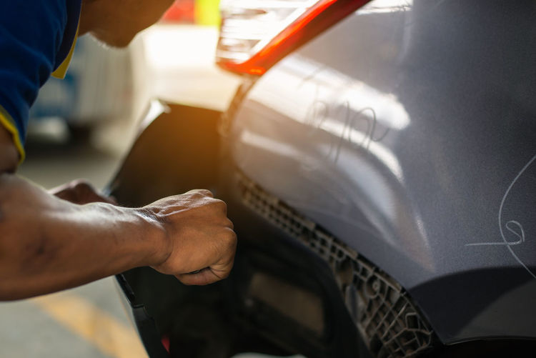 Hand Human Hand One Person Working Men Human Body Part Indoors  Occupation Car Real People Holding Motor Vehicle Close-up Mode Of Transportation Focus On Foreground Transportation Auto Repair Shop Day Midsection Mechanic