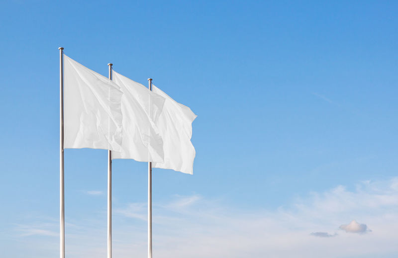 Low angle view of white flags waving against blue sky