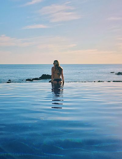 Rear view of woman swimming in infinity pool against sky during sunset