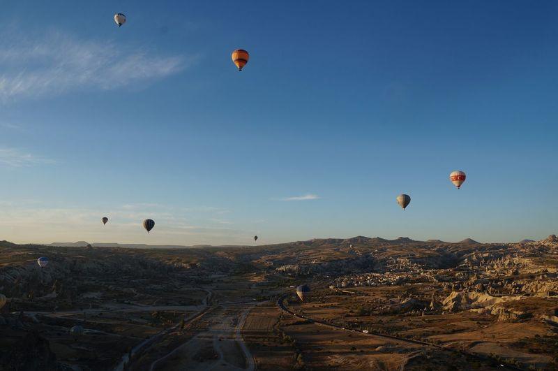 Hot Air Balloons Flying Over Cappadocia Against Blue Sky