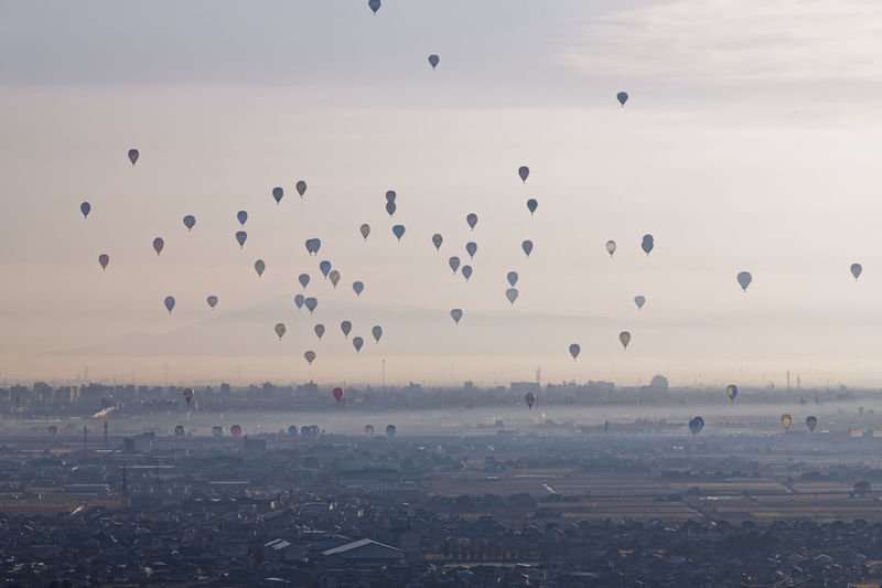 Flock of hot air balloons flying in city against sky