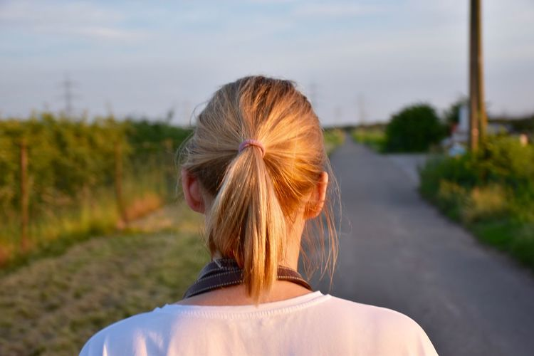 Rear View Of Woman With Ponytail Standing On Road Against Sky