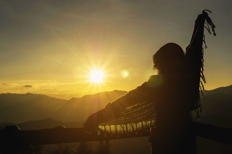 Sunset Sky Sun One Person Real People Sunlight Lifestyles Lens Flare Nature Beauty In Nature Scenics - Nature Sunbeam Orange Color Women Leisure Activity Silhouette Mountain Adult Standing Outdoors Human Arm Bright Hairstyle Arms Raised