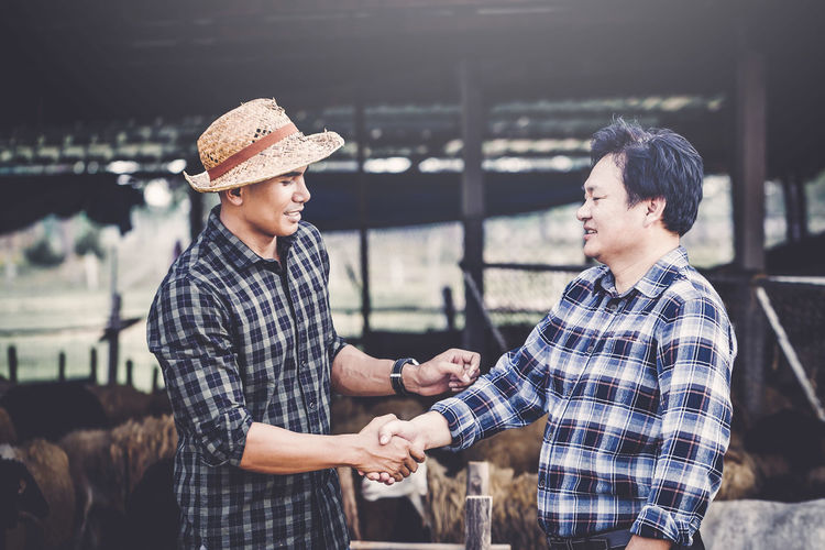 Financial advisor shaking hand with farmer at farm