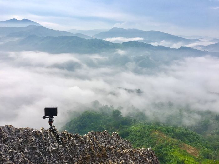 Camera on rock photographing scenic mountain range with fog