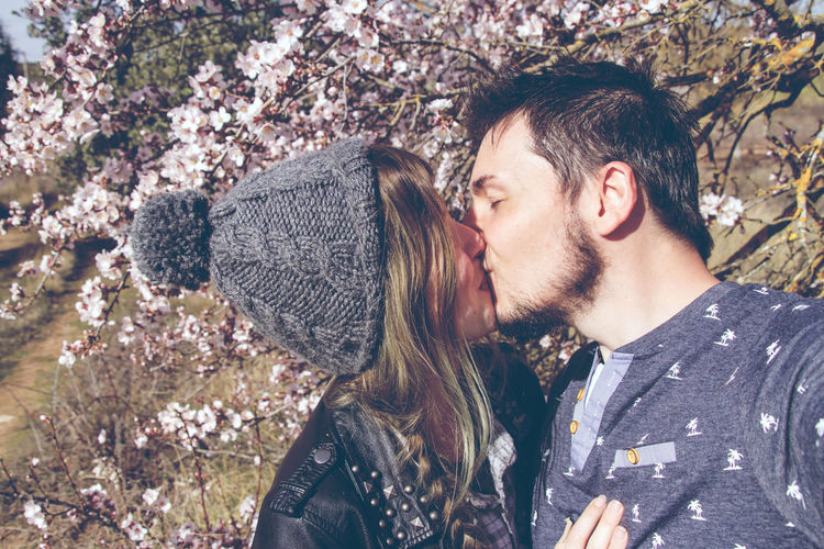 Young Couple Kissing Against Trees