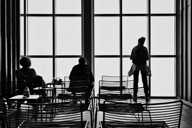 Rear view of people sitting in glass window
