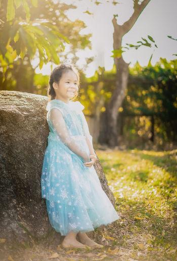 Full length of cute girl wearing dress standing by rock in park