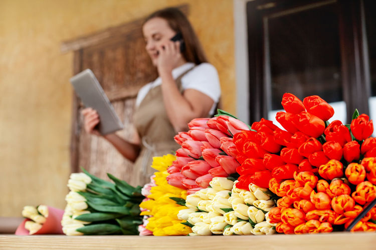 Close-up of bouquets of tulips a female florist with a tablet in her hands is talking on the phone
