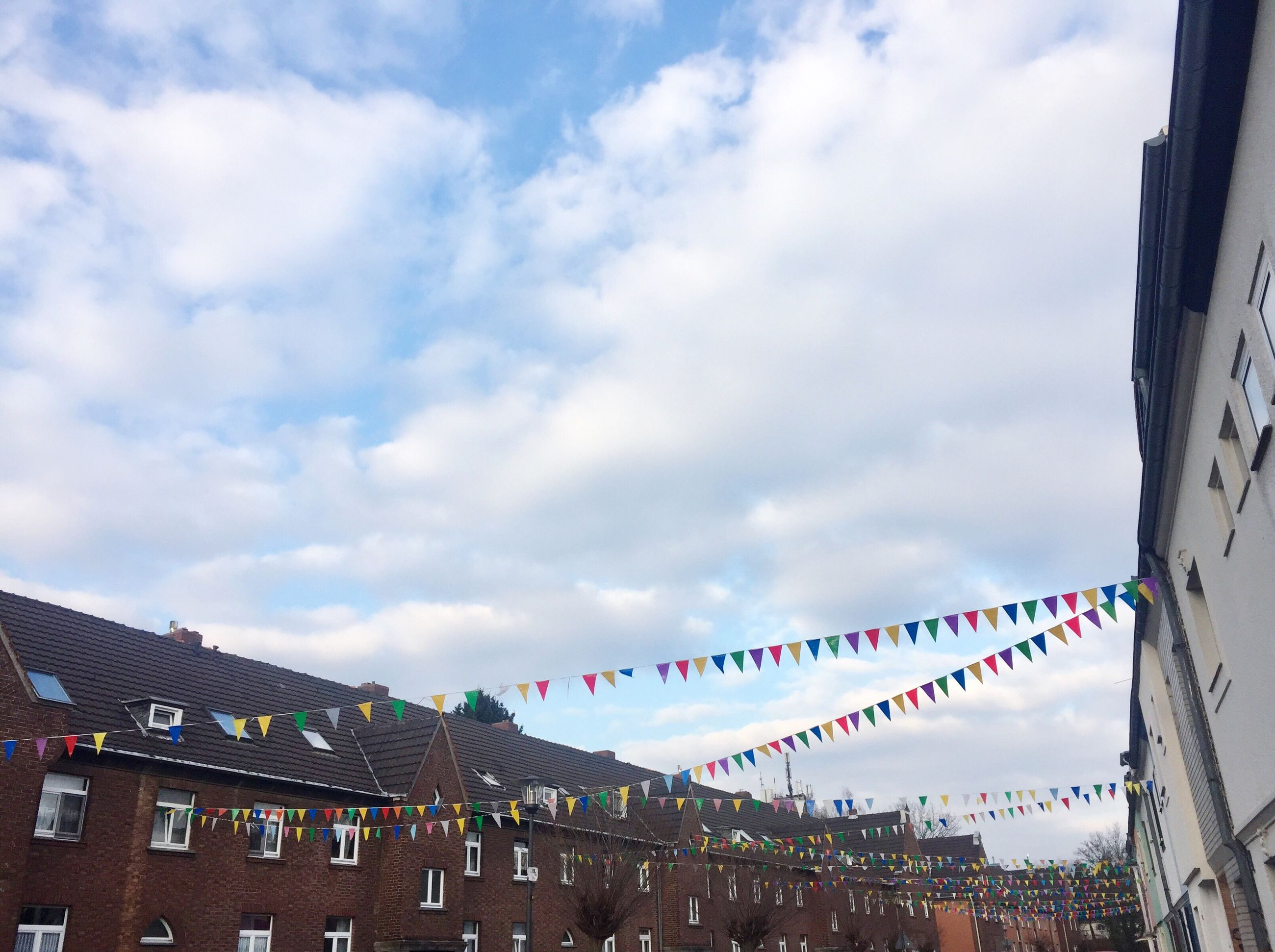 sky, multi colored, hanging, cloud - sky, low angle view, outdoors, no people, day, architecture, flag