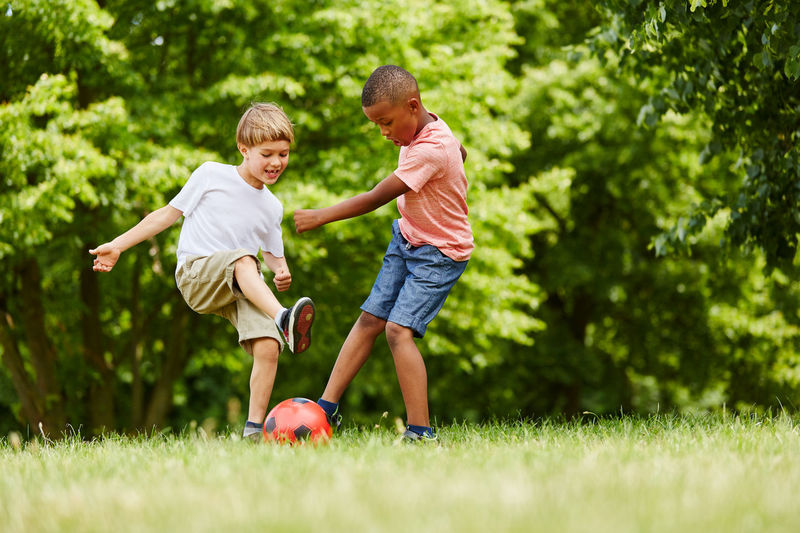 Full length of boys playing with soccer ball on grass