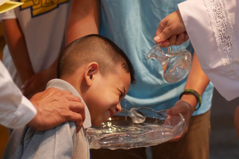 Midsection pastor giving baptism to boy in church