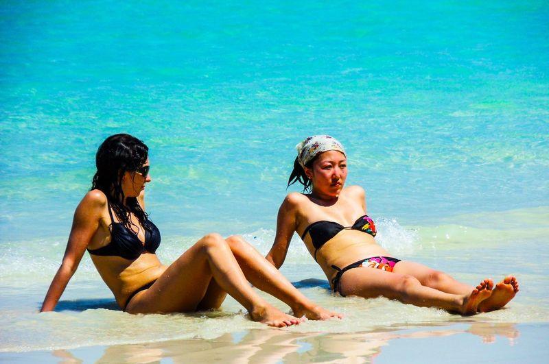 Full length of women sitting on shore at beach