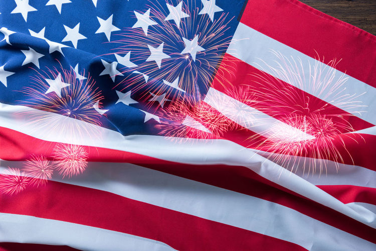 Double exposure of firework display and american flag