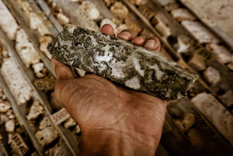 Close-up of man holding iron ore