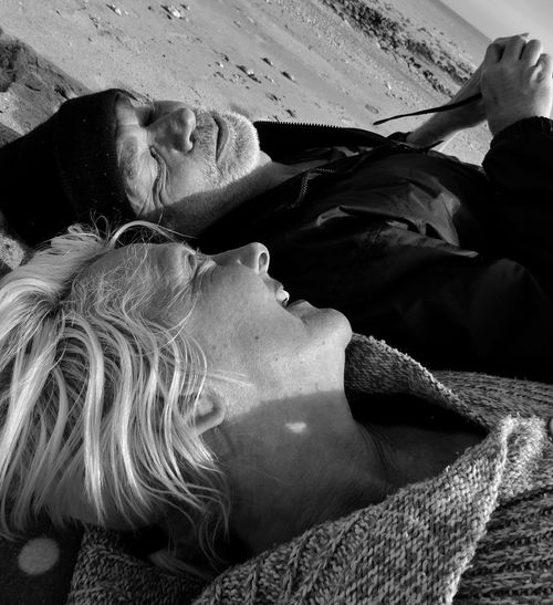 Close-up of smiling woman and man lying on sand at beach