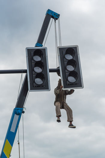 Low Angle View Of Man Hanging On Road Signal Against Sky