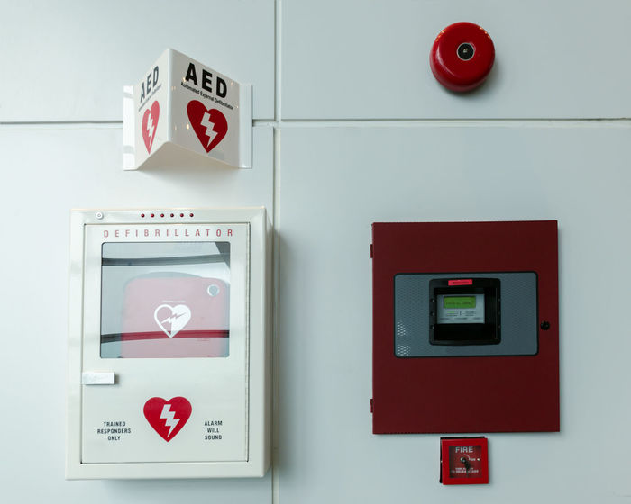General view of a life saving defibrillator. Portable automated external defibrillator (AED) and fire alarm system mounted on the wall in public restroom at airport. Fire Alarm Safety Security Protection Sign Emergency Equipment Technology Defibrillator Portable AED Alarm System Dashboard Aid Alarm Device Equipment External Panel Rescue Help Tool First Emergency Wall