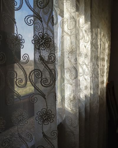 Close-up of curtain on window at home